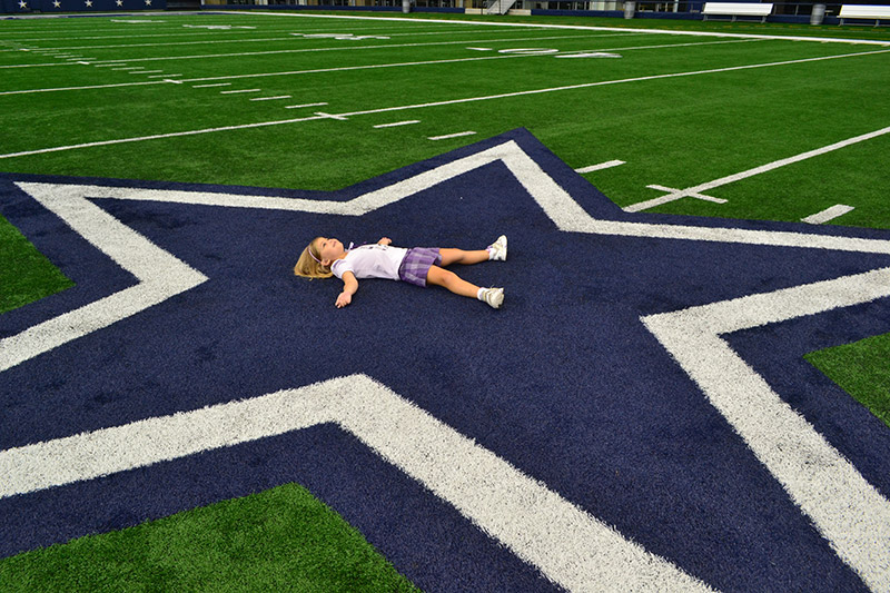 Dallas Cowboys Stadium: Alice deitada na estrela no campo