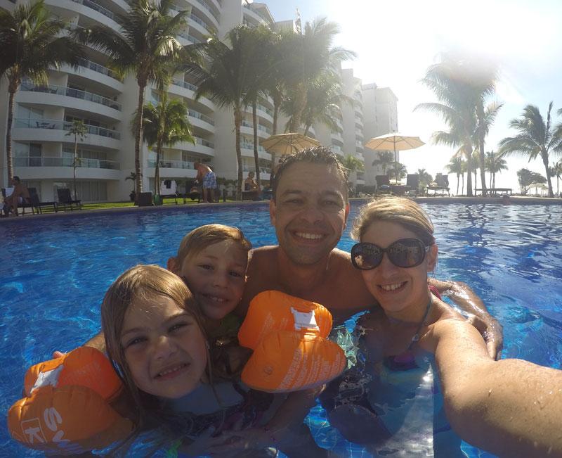 Farmacinha com remédios para viagem: família na piscina do resort